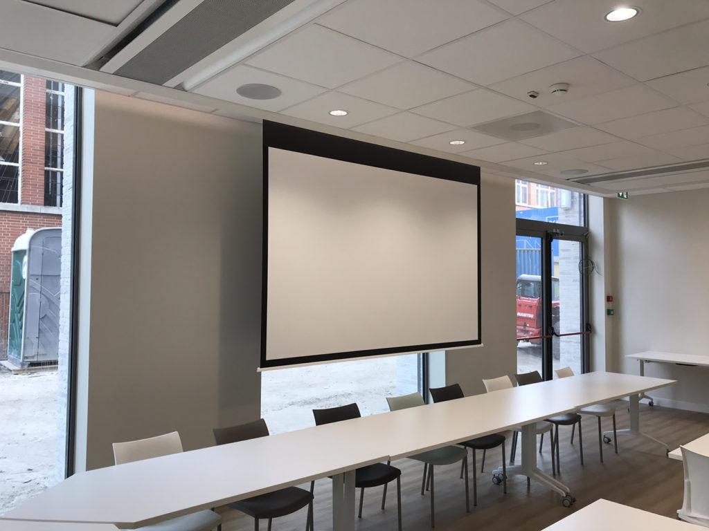 Projectiescherm voor plafondinbouw in opsplitsbare vergaderzaal