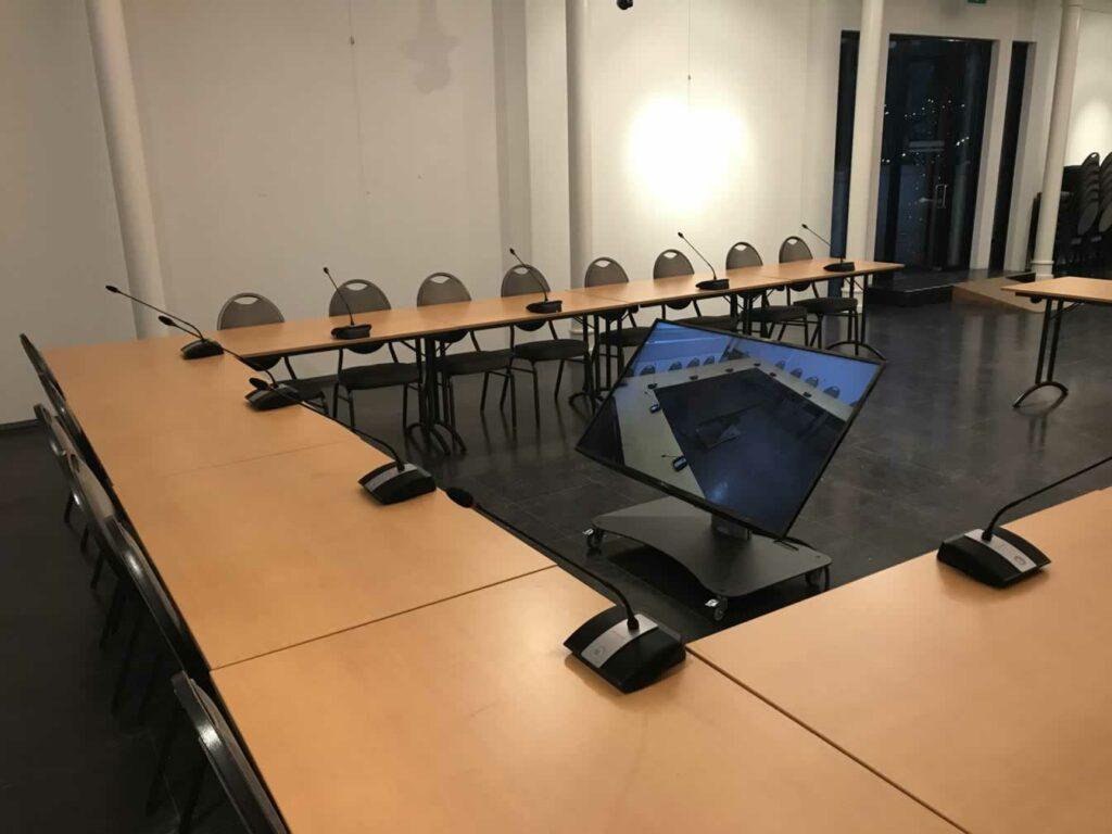 Gemeentelijke raadzaal met draadloos conferentiesysteem en herhaalscherm voor burgemeester en voorzitter